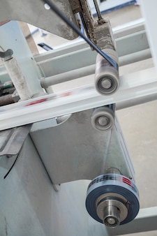 The machine glues the ribbon with the print on the profile roduction of pvc profile