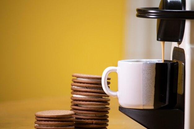 後ろにチョコレートクッキーが入ったコーヒーを作る機械