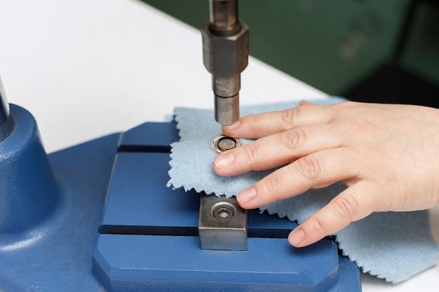 기계는 직물에 리벳을 넣습니다.