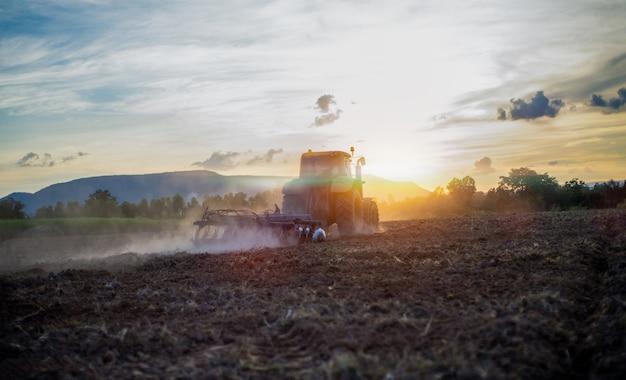 해질녘 농지에서 일하는 기계