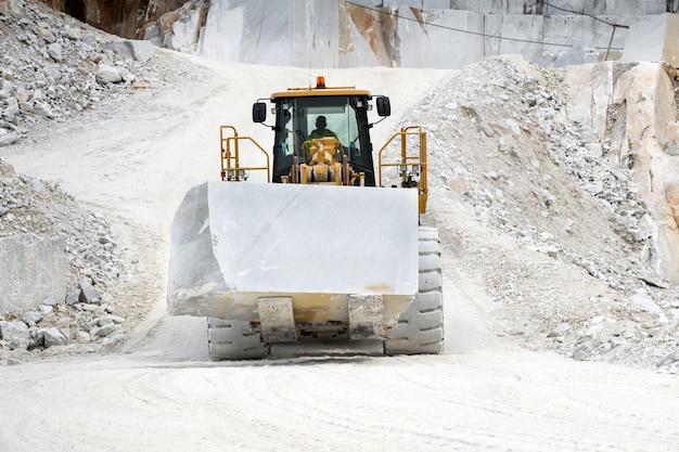 Машины перемещают блок белого каррарского мрамора в карьере в тоскане, италия
