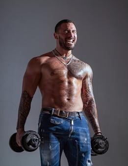Мачо уверенное лицо с мускулистым культуристом спортсмена. мускулистый мачо шесть пачек держит гантели. парень привлекательная тренировка. мускулистый торс. разработайте концепцию. совершенству нет предела.