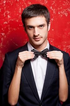 蝶ネクタイのマッチョ。彼の後ろに隠れて彼の蝶ネクタイを調整している間、赤い背景に立っている正装のハンサムな若い男