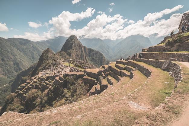 Мачу-пикчу, широкоугольный вид с террас выше с живописным небом. тонированное изображение.