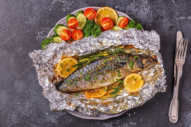 Mackerel baked in foil with vegetables on a dish, top view