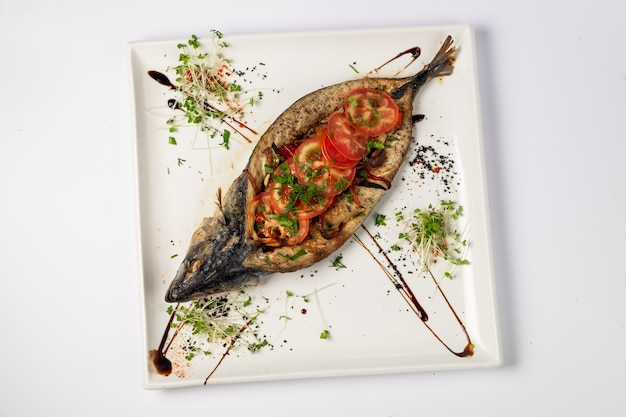 Mackerel baked with vegetables on a dish, on a white surface