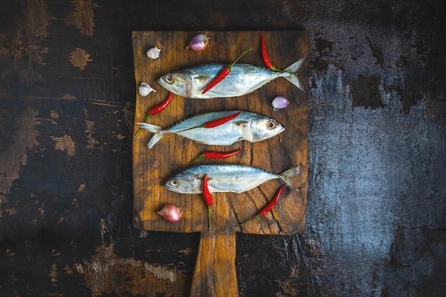 Mackerel fish on wooden chopping board