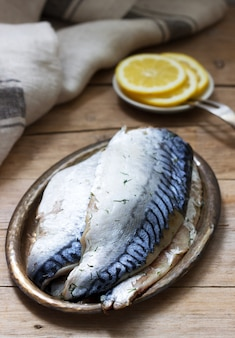 Mackerel glavrax with lemon slices on a wooden surface