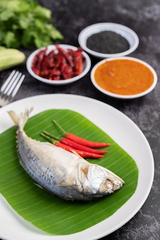 Mackerel placed on banana leaves on a white plate.