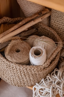 Macrame, cotton and hemp ropes in skeins. crocheting, netting handicraft objects in a basket made of jute