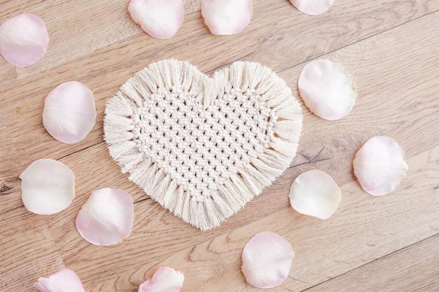 マクラメの装飾。聖バレンタインデー。ハートとバラの花びら。天然素材、綿糸。エコ装飾、装飾品、木製テーブルの手作り装飾