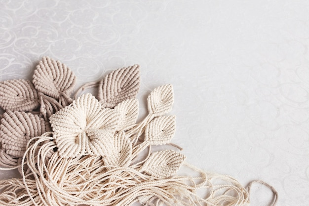 Macrame flowers and wooden stick on a white background