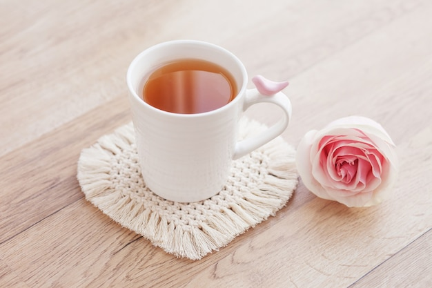 Macrame handmade hobby. tea in a cup on white macrame coaster on wooden table with rose.