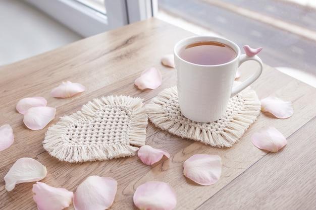 マクラメ手作りホビー。バラの花びらと木製のテーブルの上の白いマクラメコースターのカップのお茶。フードスタイリスト。エコマクラメの家の装飾。聖バレンタインデー