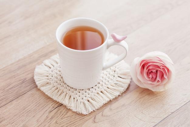 マクラメ手作りホビー。バラと木製のテーブルの上の白いマクラメコースターのカップのお茶。
