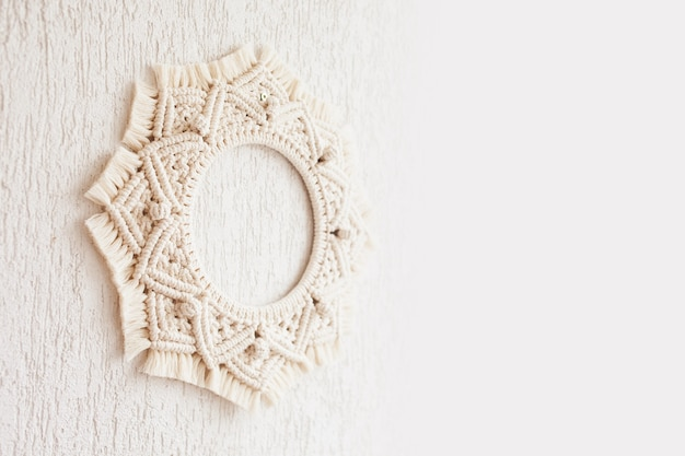 Macrame mandala. macrame wreathe on a white background close up. natural cotton thread. eco home decor.  copy space
