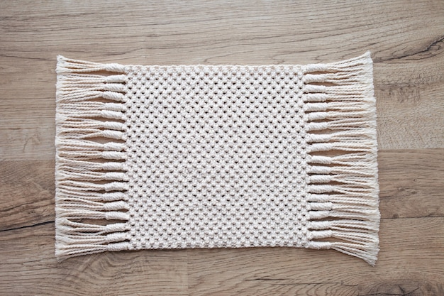 木製のテーブルにマクラメ絨毯や床のカーペット。手作りベージュマクラメ背景。マクラメのテクスチャ、環境に優しい、モダンな編み物。