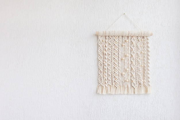 Macrame wallhanging with wooden beads. wall panel of cotton threads in natural color. macrame technique for eco home decor. modern macrame wall hanging will add cozy atmosphere. copy space