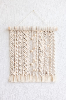 Macrame wallhanging with wooden beads. wall panel of cotton threads in natural color. macrame technique for eco home decor and wedding decoration. modern macrame wall hanging will add cozy atmosphere
