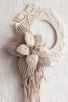 Macrame wreath with big cotton flower on a white decorative plaster wall