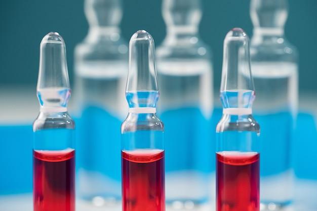 Макроампулы из стекла с красным препаратом для внутривенного и внутримышечного введения больным горизонтальным крупным планом