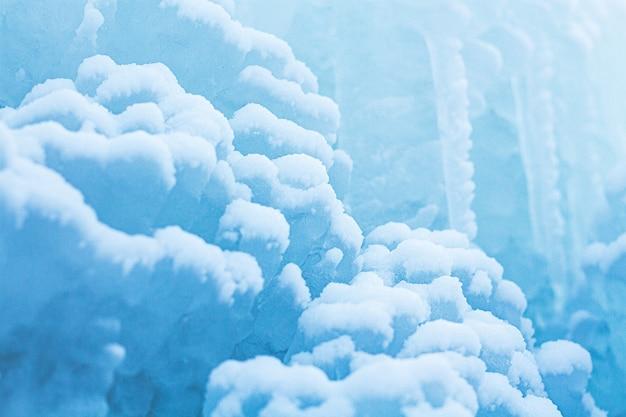 雪とつららのマクロ背景。クローズアップの冬の風景。美しい青い氷と雪の形成。