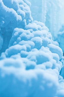 Макро фон из снега и сосулек. крупным планом зимний пейзаж. красивые голубые ледяные и снежные образования.