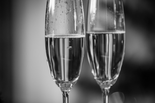 Macro black and white image of champagne bubbles in two glasses