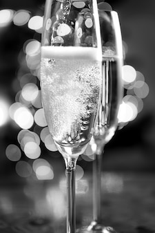 Macro black and white photo of champagne poured into glasses