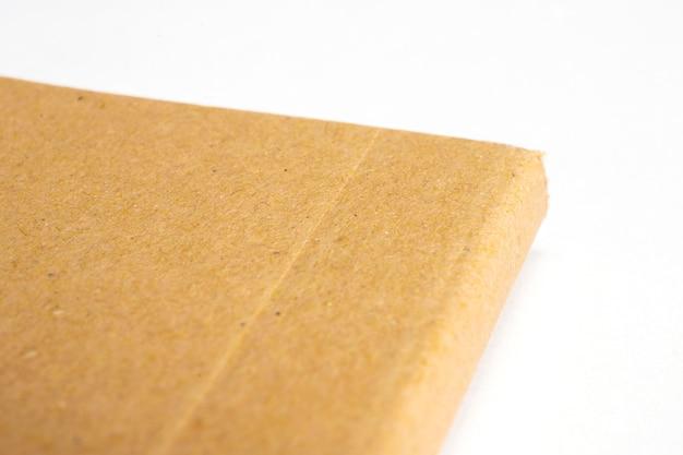 Macro dell'angolo in bianco del taccuino con la copertina dura del cartone isolata su bianco