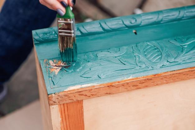 Макро-кисть с синей или зеленой краской обновляет старую деревянную мебель для повторного использования и защиты окружающей среды