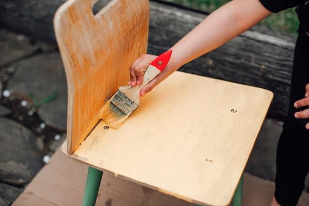 Макро детская рука с кистью красит небольшой старый деревянный стул желтой краской