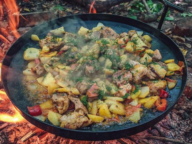 Макро крупным планом жареный картофель с мясом и овощами на сковороде над огнем