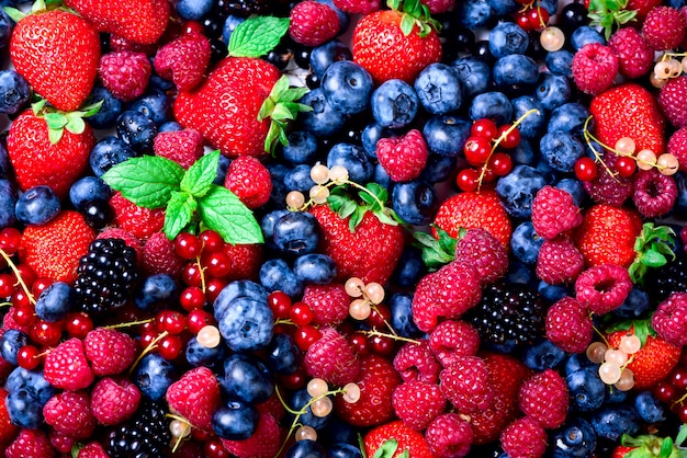 Macro colorful berries background. summer food frame, border design. assorted mix of strawberry, blueberry, raspberry, blackberry, currant, mint.