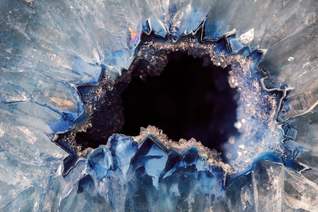 Macro details of a blue agate mineral on reflective surface. agate has a typical zoned structure and is visible even to the naked eye.
