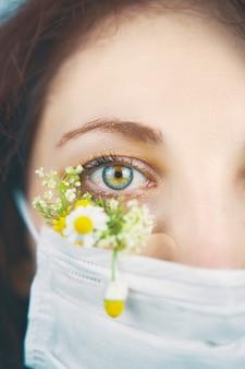マクロ目の肖像画。スタジオでカメラを見ている花の花のフェイスマスクで若い魅力的な女性