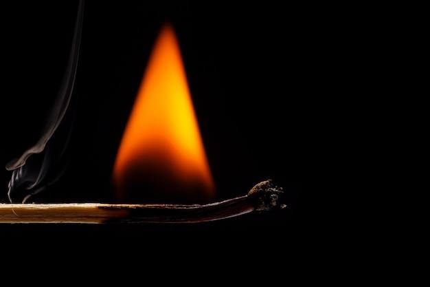 Macro fire burning on matchstick.