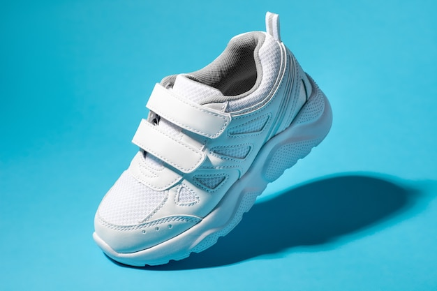Macro flying white child sneakers with velcro fasteners isolated on a blue background with hard light