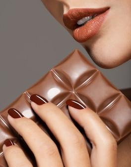 茶色の爪とチョコレートのバーを持つ女性の手のマクロ画像
