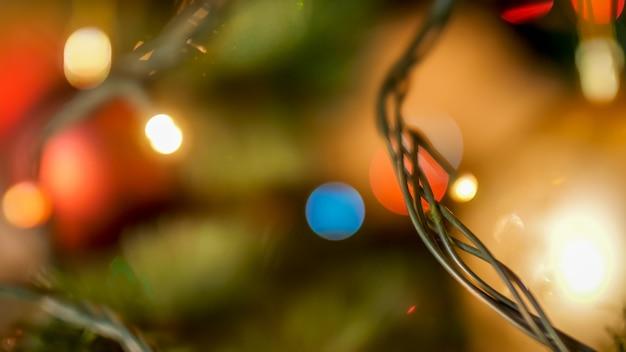 Макро изображение светодиодной гирлянды рождественских огней, висящей на елке