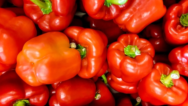 Макро-изображение серий красного перца, лежащего на прилавке магазина. текстура или узор из свежих спелых овощей