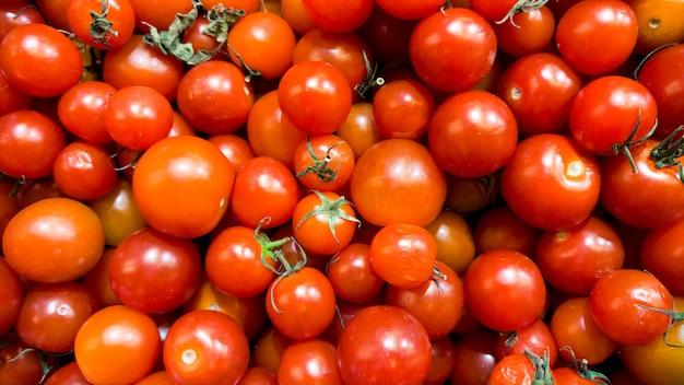 Макро-изображение серий красных маленьких помидоров черри на прилавке в овощном магазине. текстура или узор из свежих спелых овощей