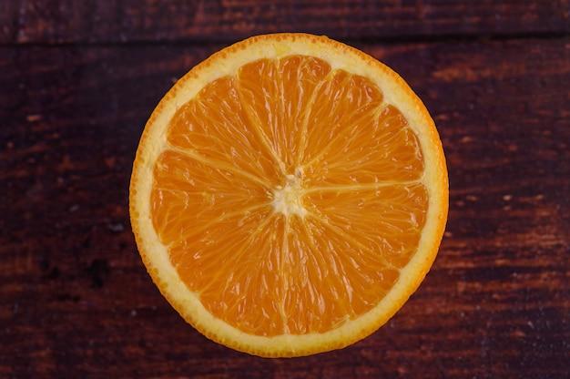Macro image of ripe orange, on wood table