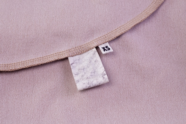 Macro mock fabric blank white tag for clothing care instructions and tag with size xs sewn into the clothing seam