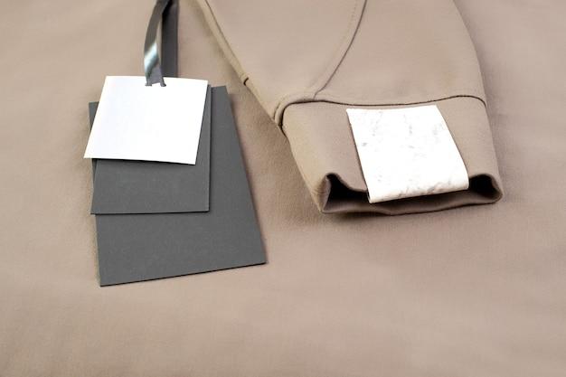 Макро макет пустой черно-белой бумажной бирки на черной атласной ленте возле рукава с нашивкой для логотипа бренда