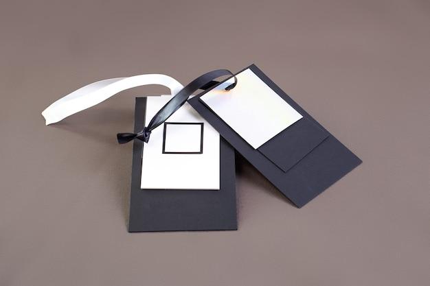 Макро макет пустой черно-белой бумажной бирки с черно-белой атласной лентой для логотипа бренда на зеленом хлопковом материале