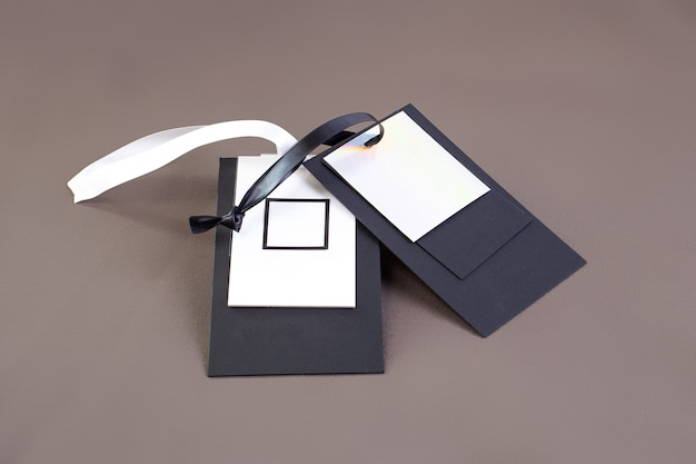 Macro mock up empty black and white paper tag with black and white satin ribbon for brand logo on green cotton material