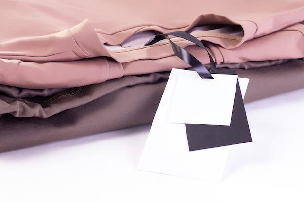 マクロは、空の紙の黒と白のラベルをモックアップするか、tシャツやパーカーのスタックにタグを付けます