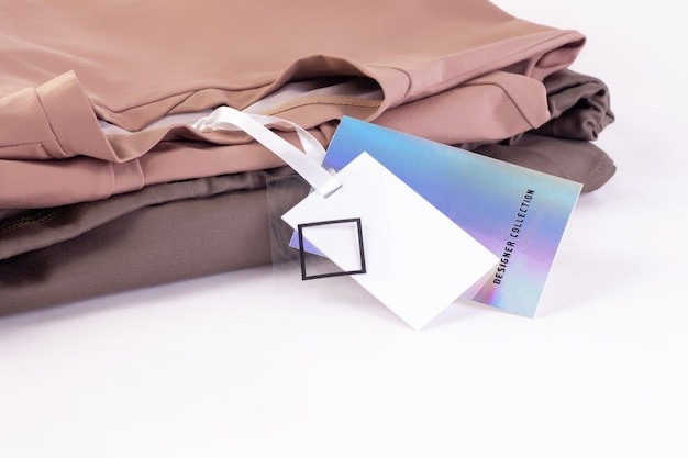 Macro mock up empty paper metallic shining iridescent label or tag on a stack of clothing isolated