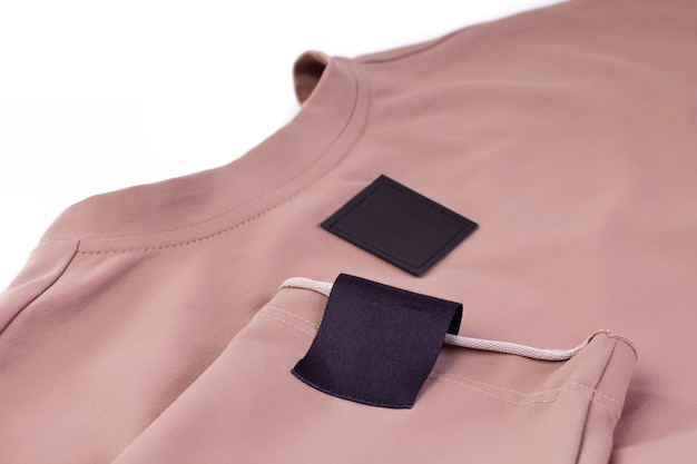 Macro mock up fabric blank black patch for the brand logo on the arm and black eco leather tag on the beige sweater